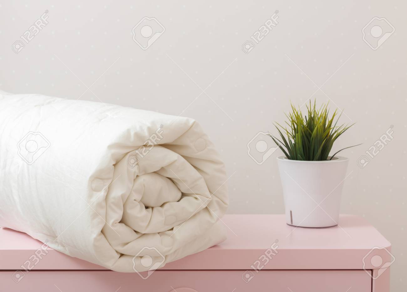 A rolled up duvet is lying on the dresser. Blanket for a bed - 114417276