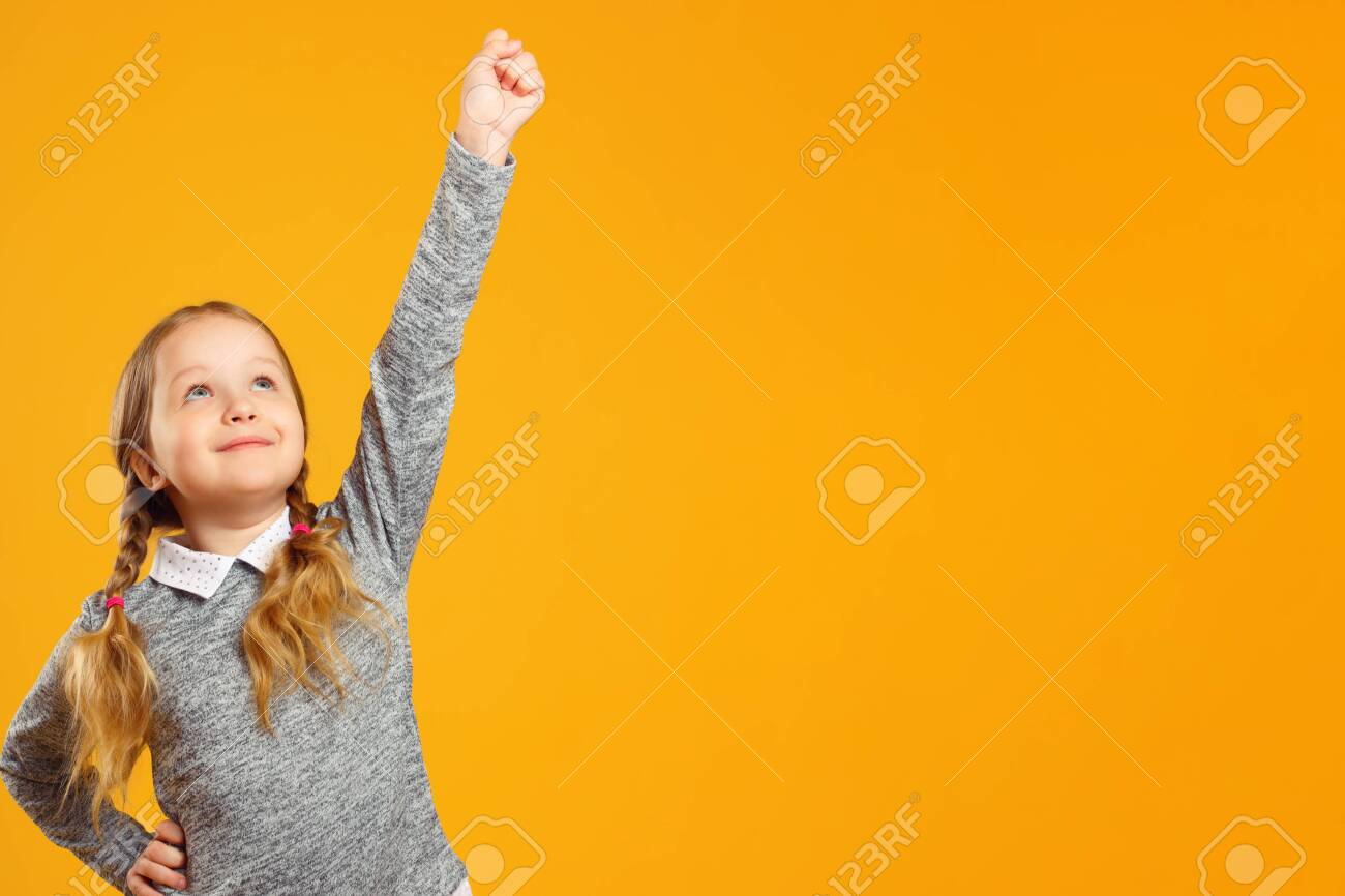 Closeup portrait of a little girl on a yellow background. The child raised his hand up. The concept of success and education. Copy space. - 124360817