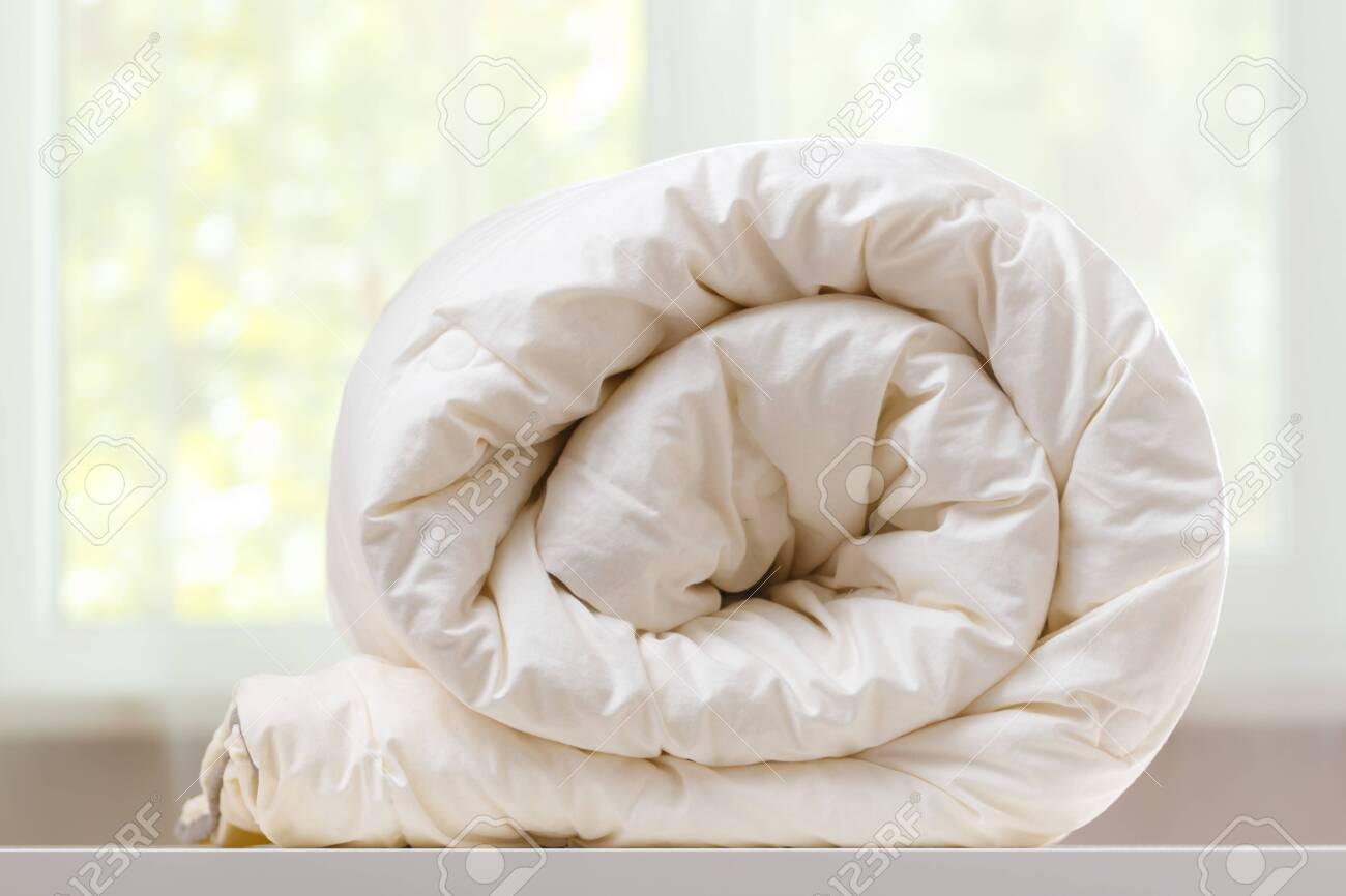 A folded rolls duvet is lying on the dresser against the background of a blurred window. Household. - 128112277