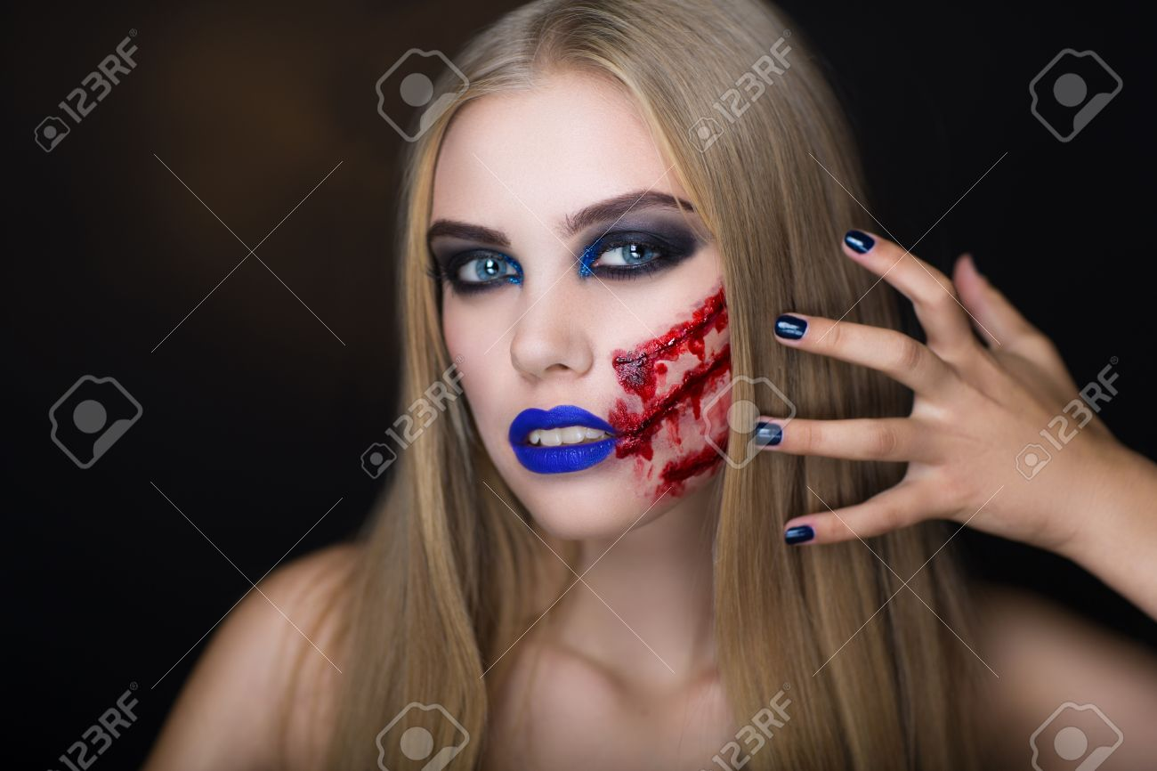 Beautiful girl with creative make up for the halloween party bright colors faceart