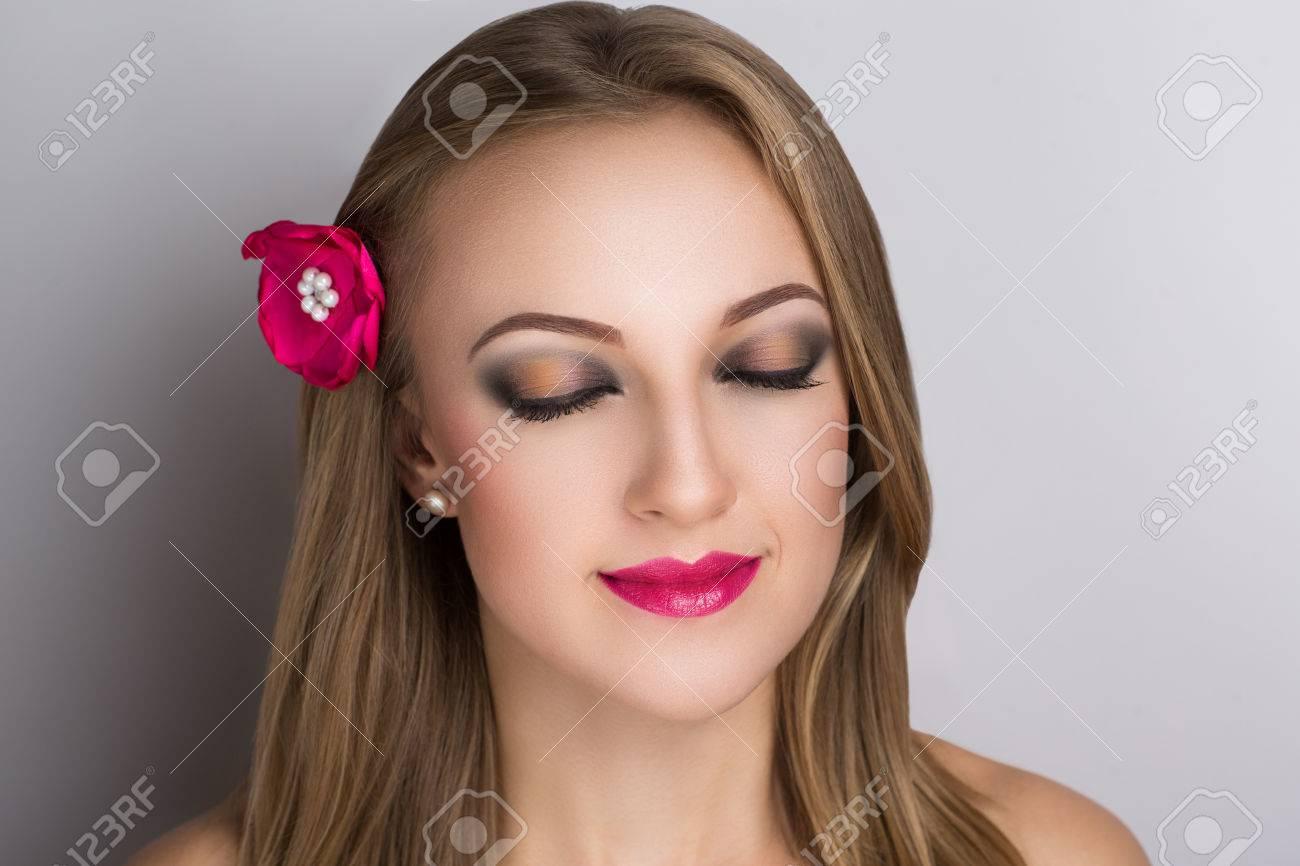 Bonne humeur souriante femme printemps. Fashion épingle nouveau style, élégant petite fleur rose. visage attrayant cheveux raides maquillage