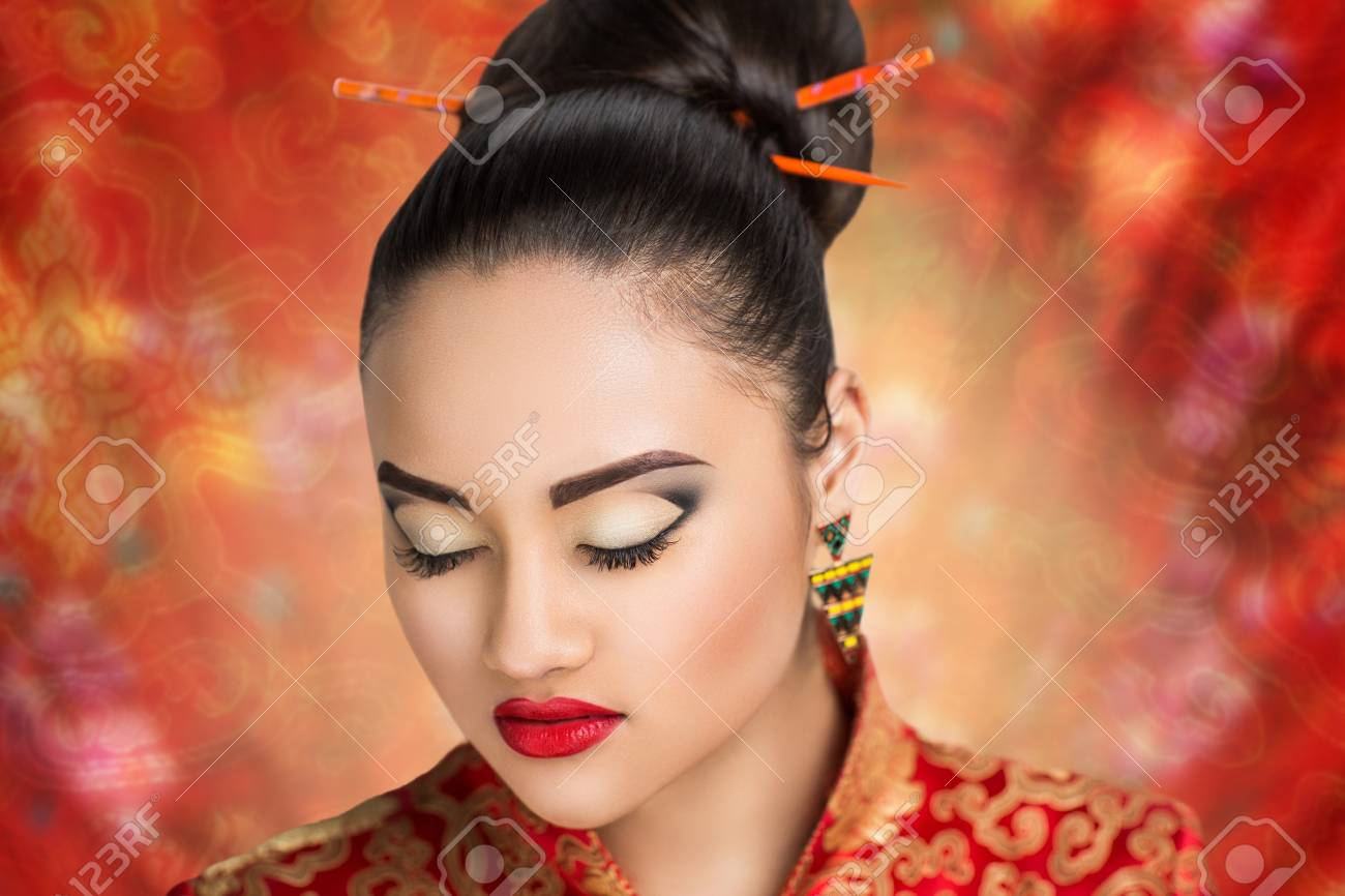 Stock Photo - Young beautiful girl, lady, woman, model, Asian. Bright makeup, expressive eyes, arrows, bright red lips. Japan, China, tradition,customs, ...