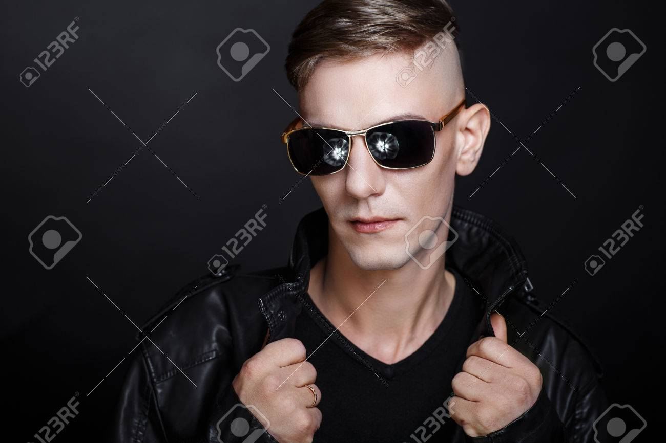 e40871617fc Stock Photo - Stylish man wearing black sunglass holding big eye glasses  collection. Fashion sexy bad boy or rocker. Brown hair guy with fashionable  haircut ...