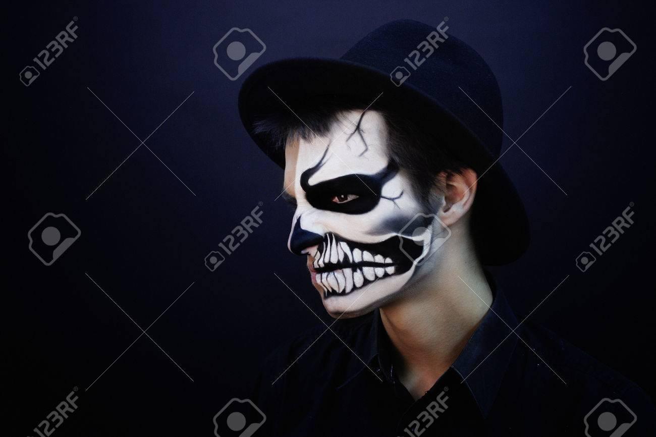 Hombre creativo con maquillaje para la fiesta de Halloween. La idea  original para el cráneo blanco y negro de Halloween en su cara, la mitad de  la