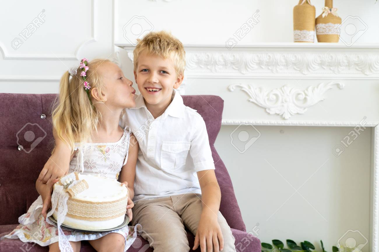 1061b0d6fc Cute little boy and beautiful girl are sitting on a chair together. Younger  sister congratulates