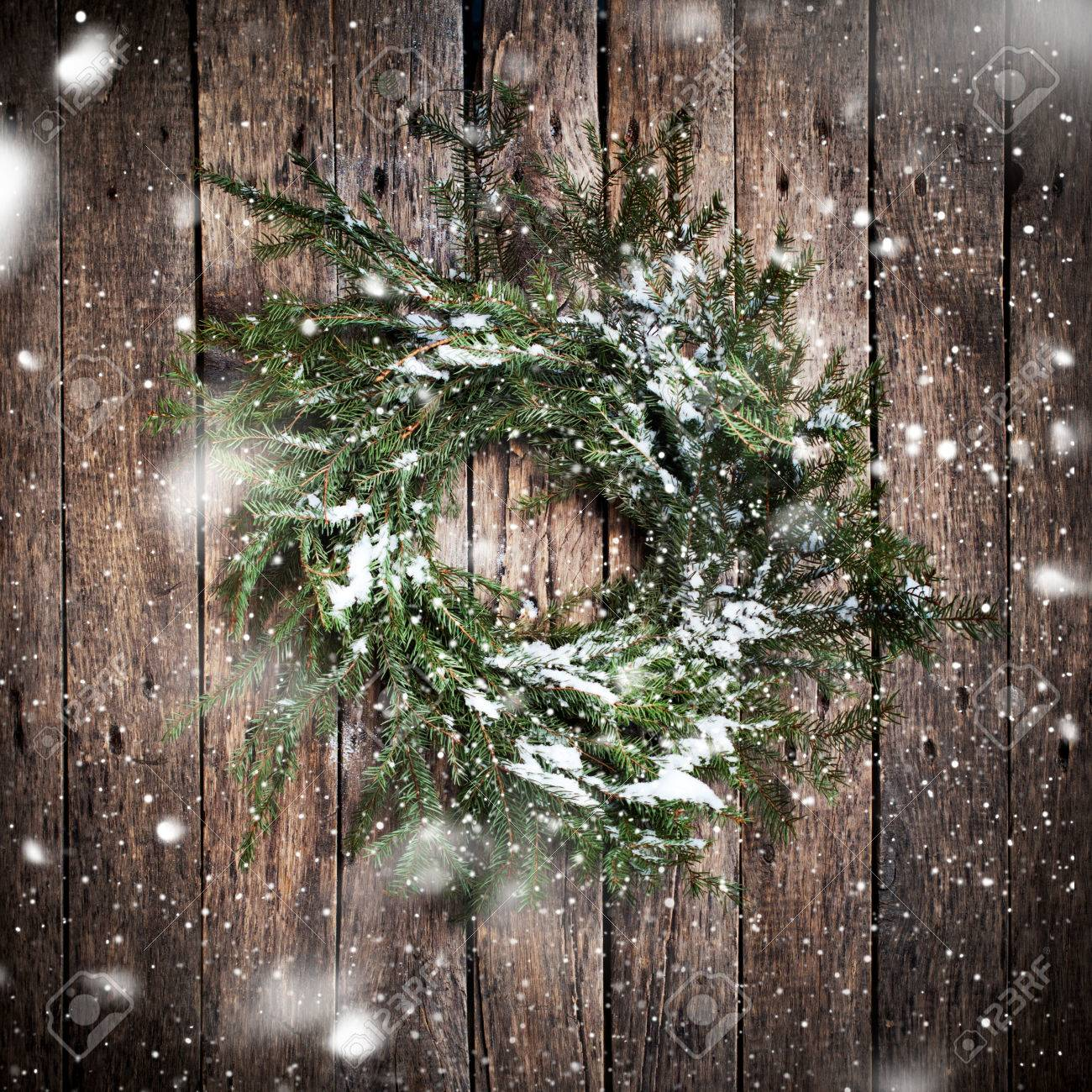 Green Natural Wreath on Wooden Background with drawing Falling Snow. Vintage Style - 46933221