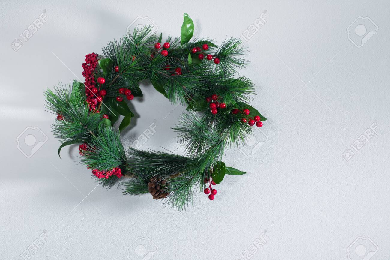 Holiday green Christmas decoration wreath on gray vintage wall. Happy New Year greeting card. Winter xmas theme - 137897687