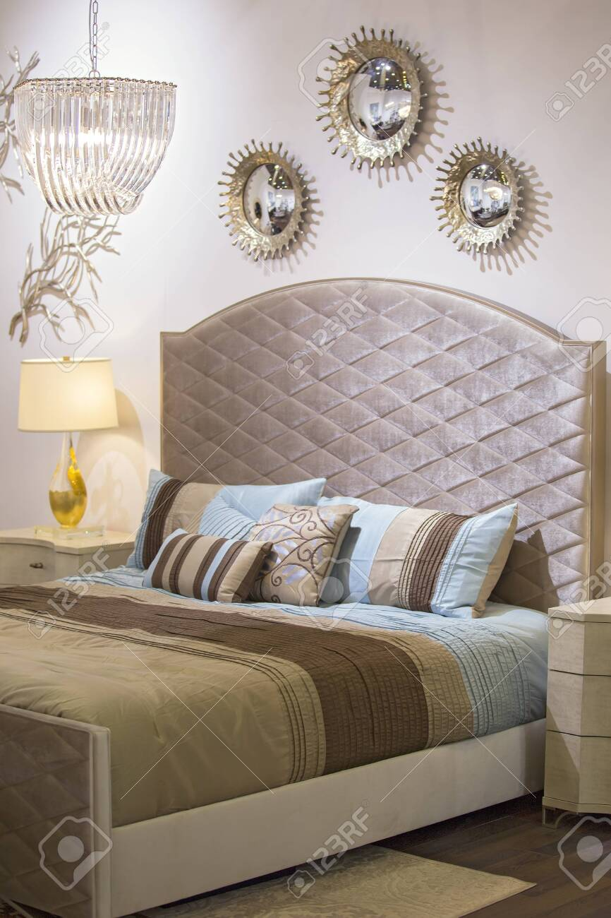 Fashionable modern bedroom, bed, chandelier, mirrors on the wall,