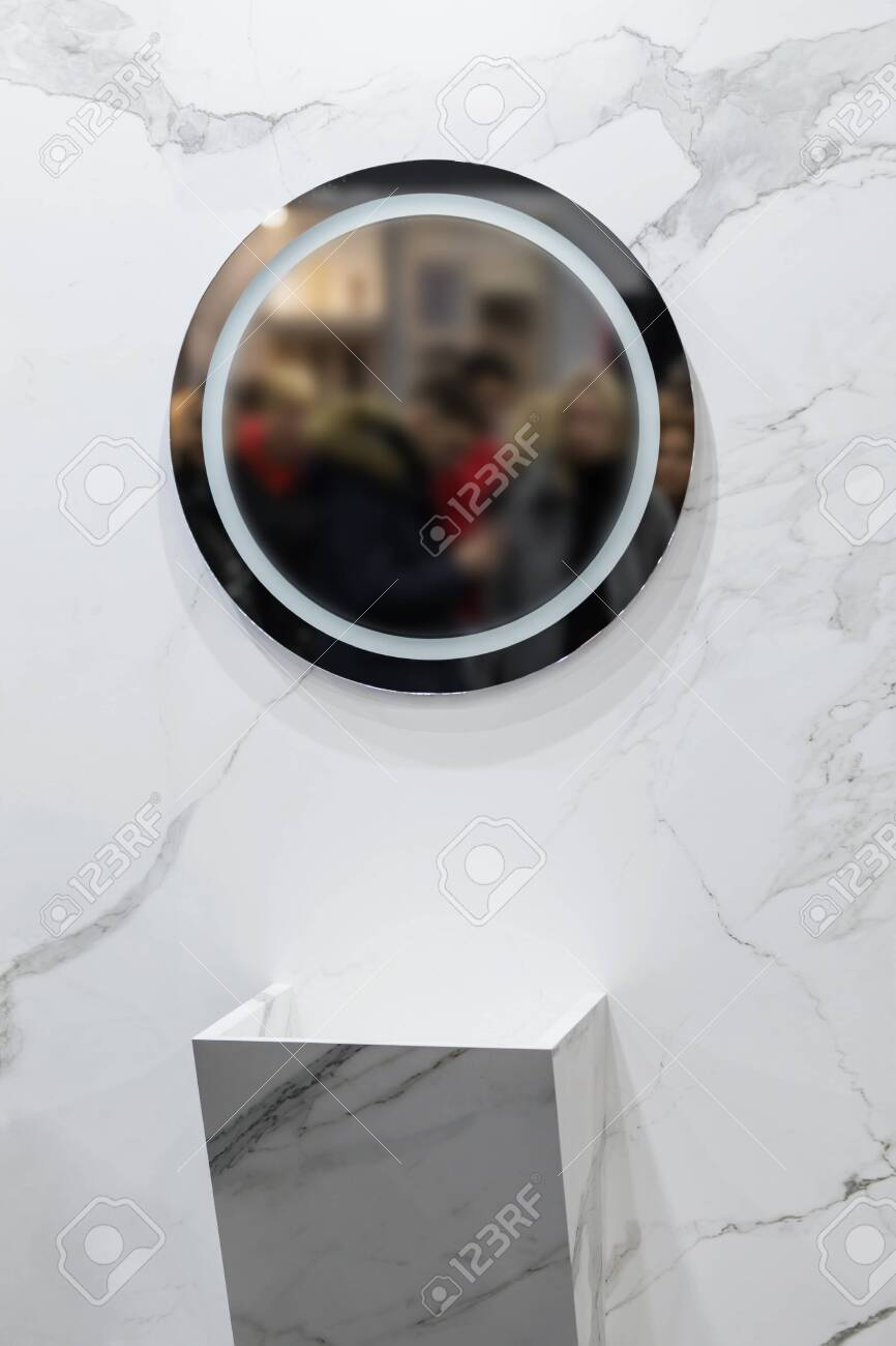 Marble sink on the background of a marble wall, white bathroom completely in marble with round mirror. - 142027168