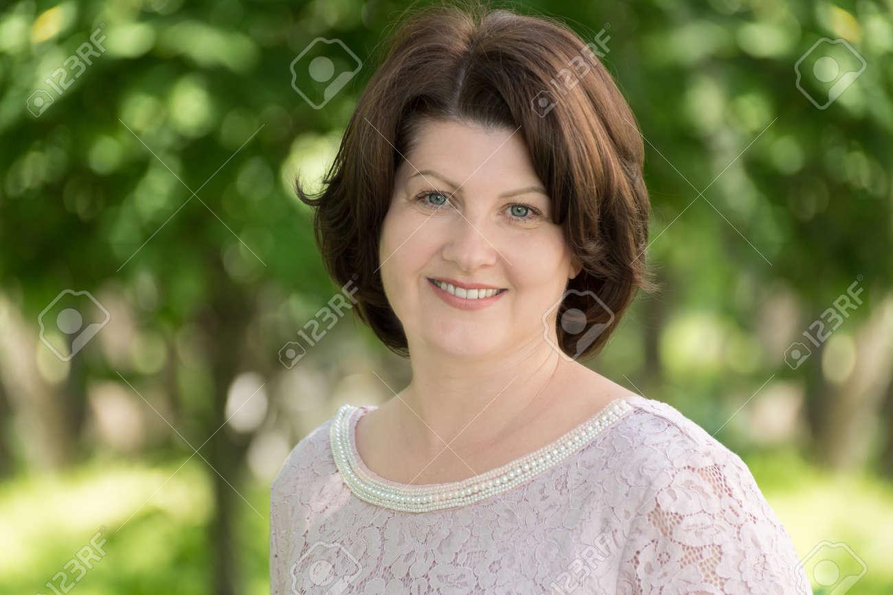 brunette woman near tree in summer park - 151722314