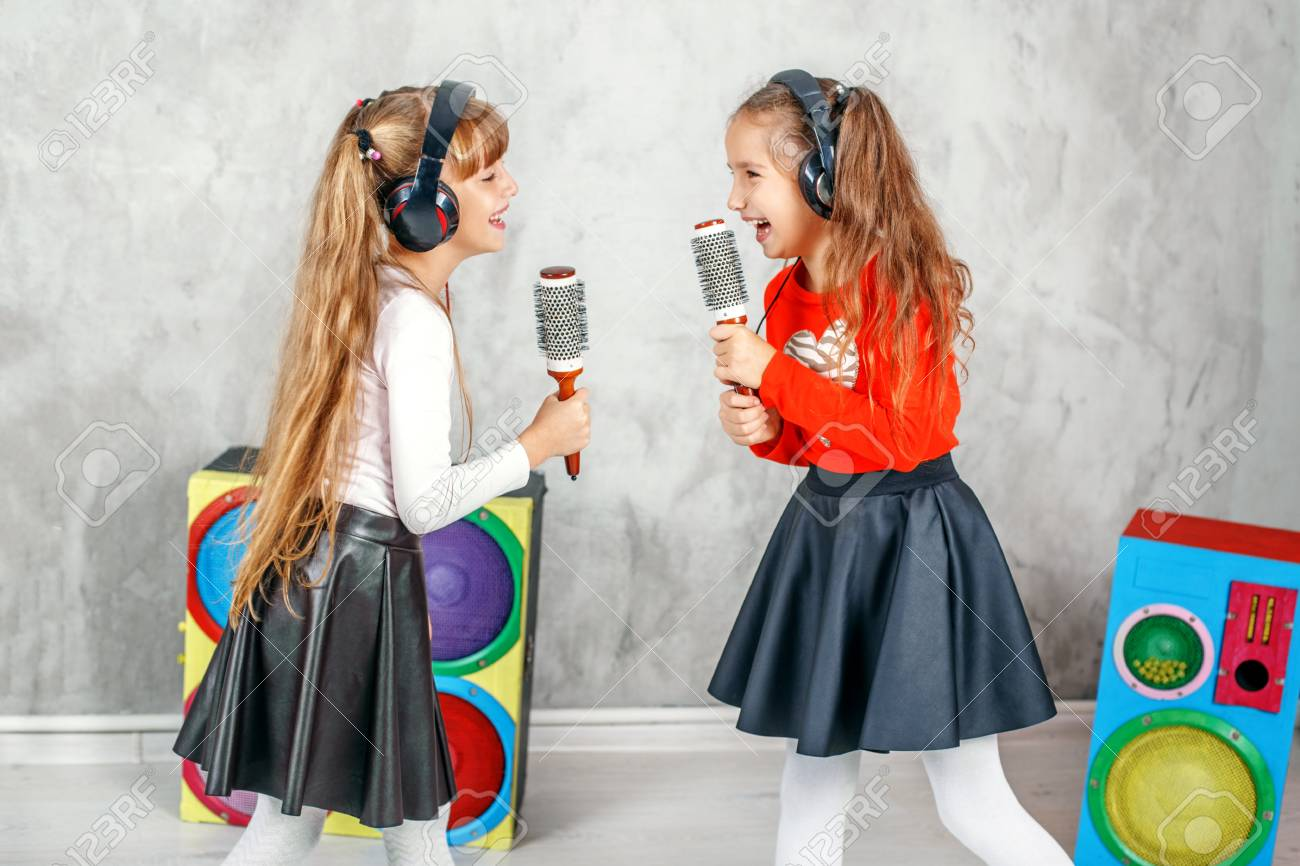 Funny kids singing and listening to music on headphones  The