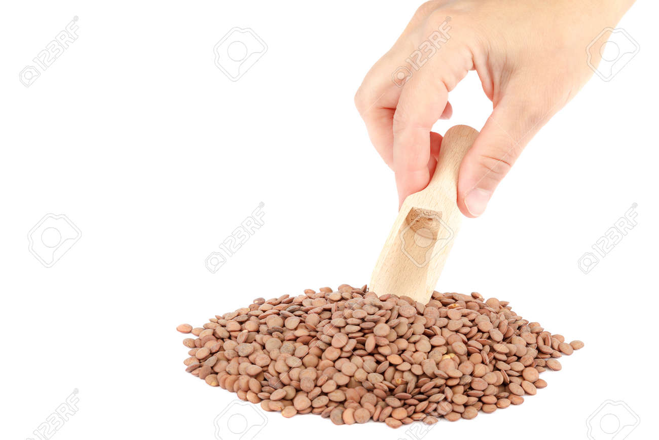 Lentil grains and a female hand with a wooden scoop isolated on a white background. - 157708112