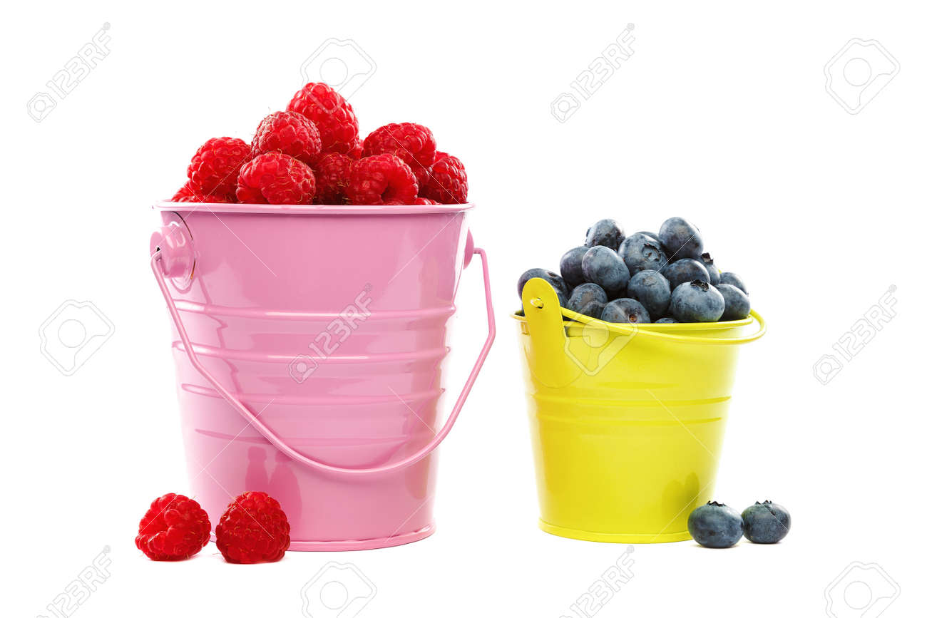 Fresh blueberries and raspberries in buckets isolated on a white background. - 157708318