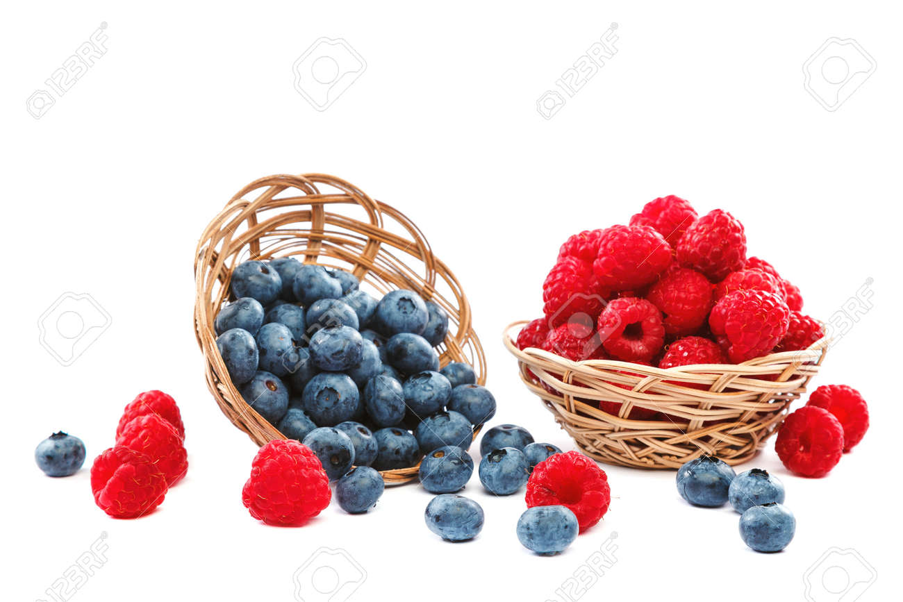 Fresh blueberries and raspberries in wicker baskets isolated on a white background. - 157708602