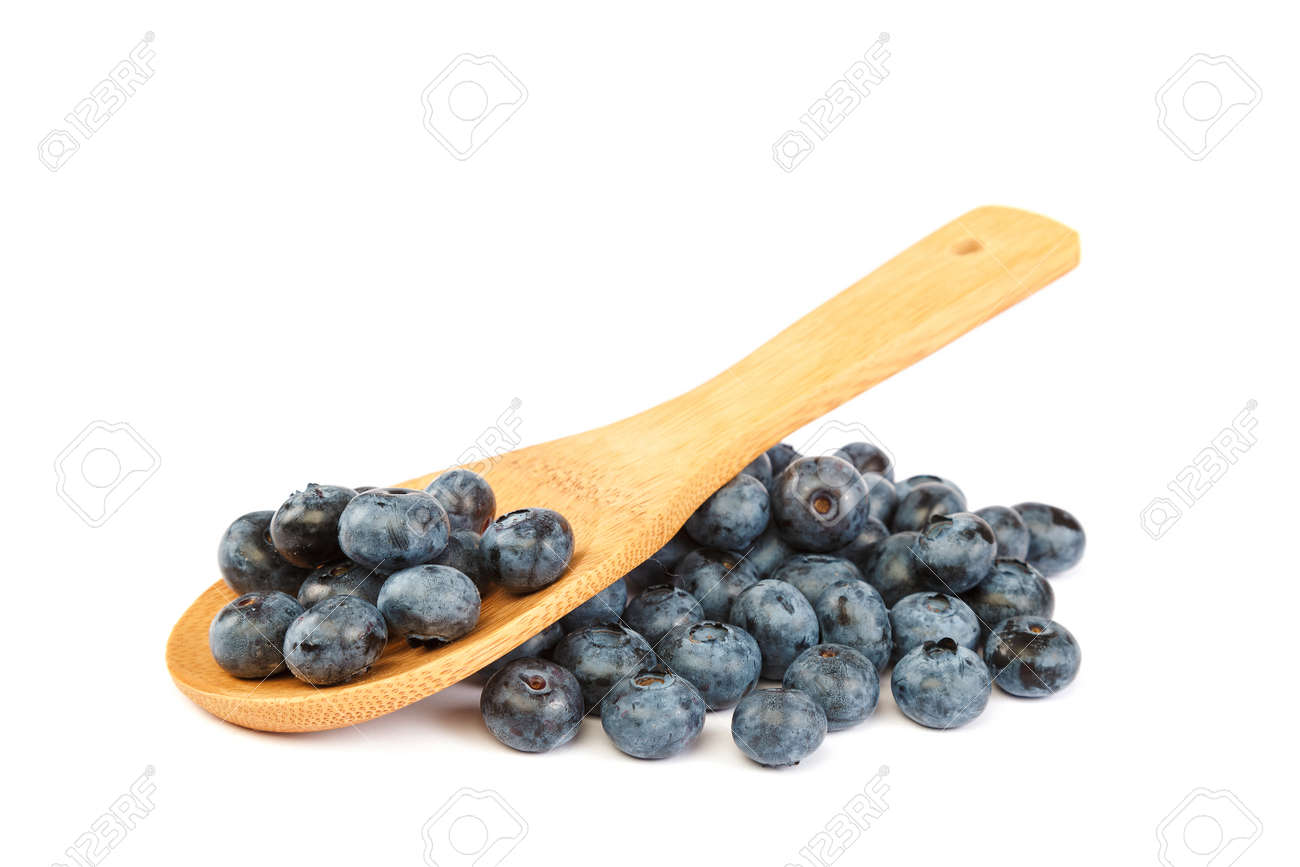 Fresh blueberries with a wooden spoon isolated on a white background. - 157708611