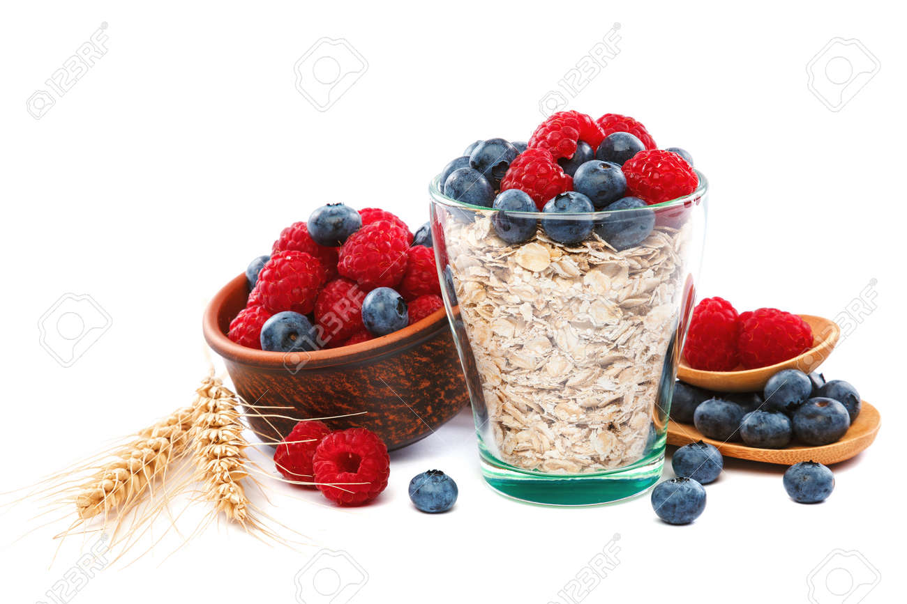 Fresh blueberries and raspberries, oatmeal in a bowl with a wooden spoon isolated on a white background. - 154785869