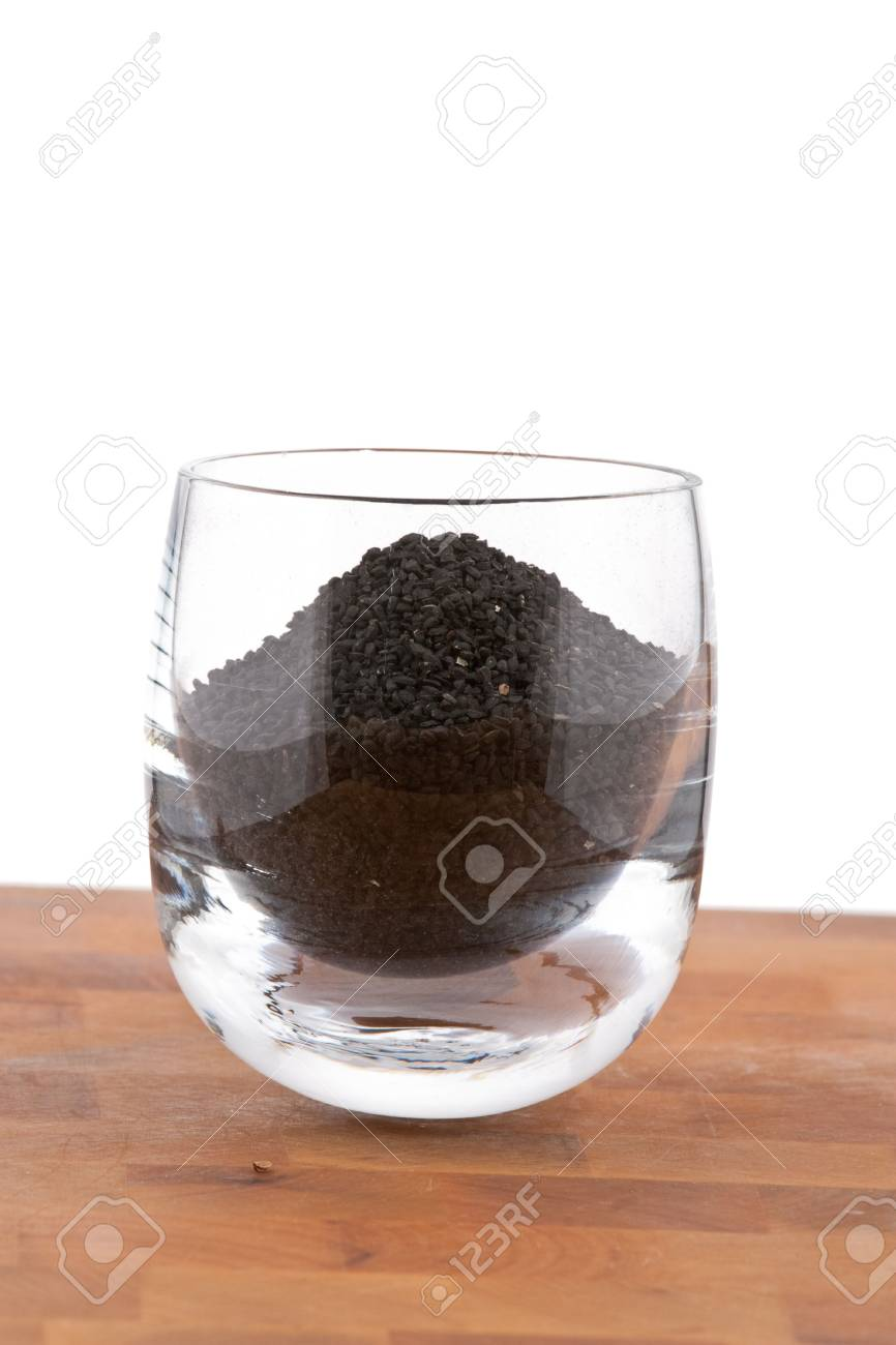 black onion seeds in glass on wooden table, white background Stock Photo - 4694163