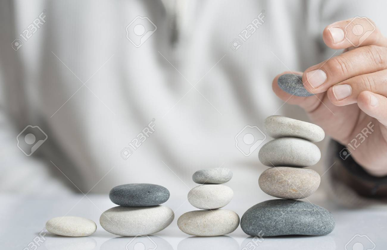 Horizontal image of a man stacking pebbles on a table with copyspace for text. Concept of risk management and wealth. - 63351380