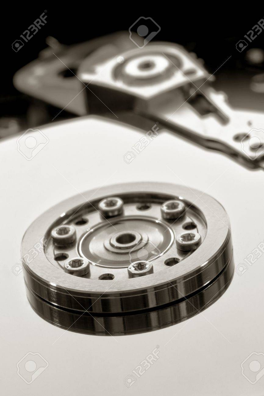 Platter disc, spindle hub, and actuator arm inside an open computer hard drive Stock Photo - 4097242