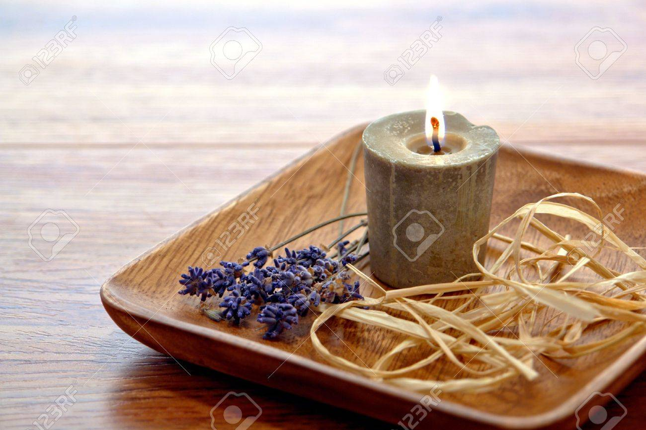 Aromatherapy organic rustic candle burning in a wood dish with