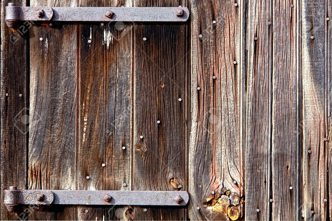 Stock Photo - Weathered old wood barn door with vintage iron hinges - Weathered Old Wood Barn Door With Vintage Iron Hinges Stock Photo
