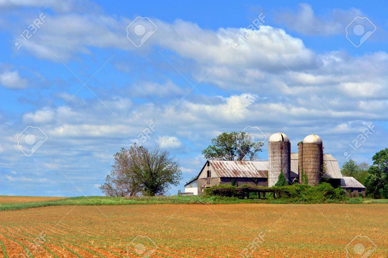 Old Farm Barn Building With Silos And Recently Planted Agricultural Field Stock Photo