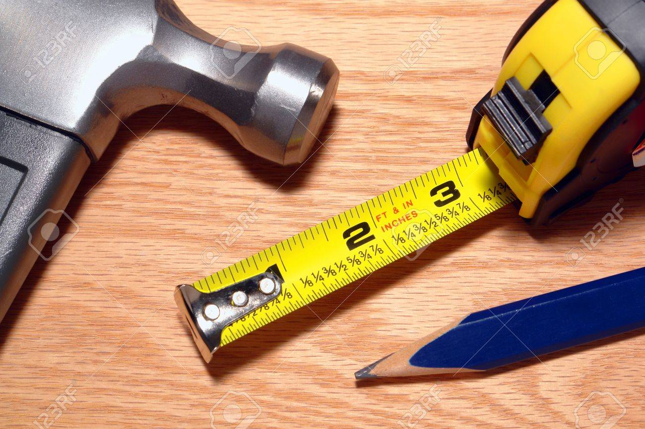 Carpenter Tools On Wood Board With Retractable Tape Measure And