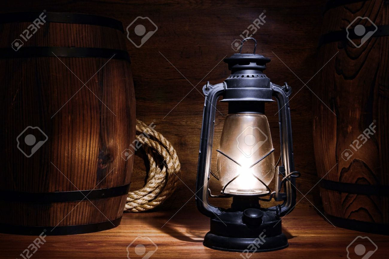Old Kerosene Lantern Burning With Bright Flame Between Wood Barrels In A  Vintage Country Barn Warehouse