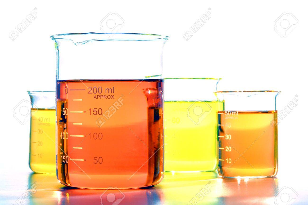 assorted sizes glass scientific beakers filled with orange and