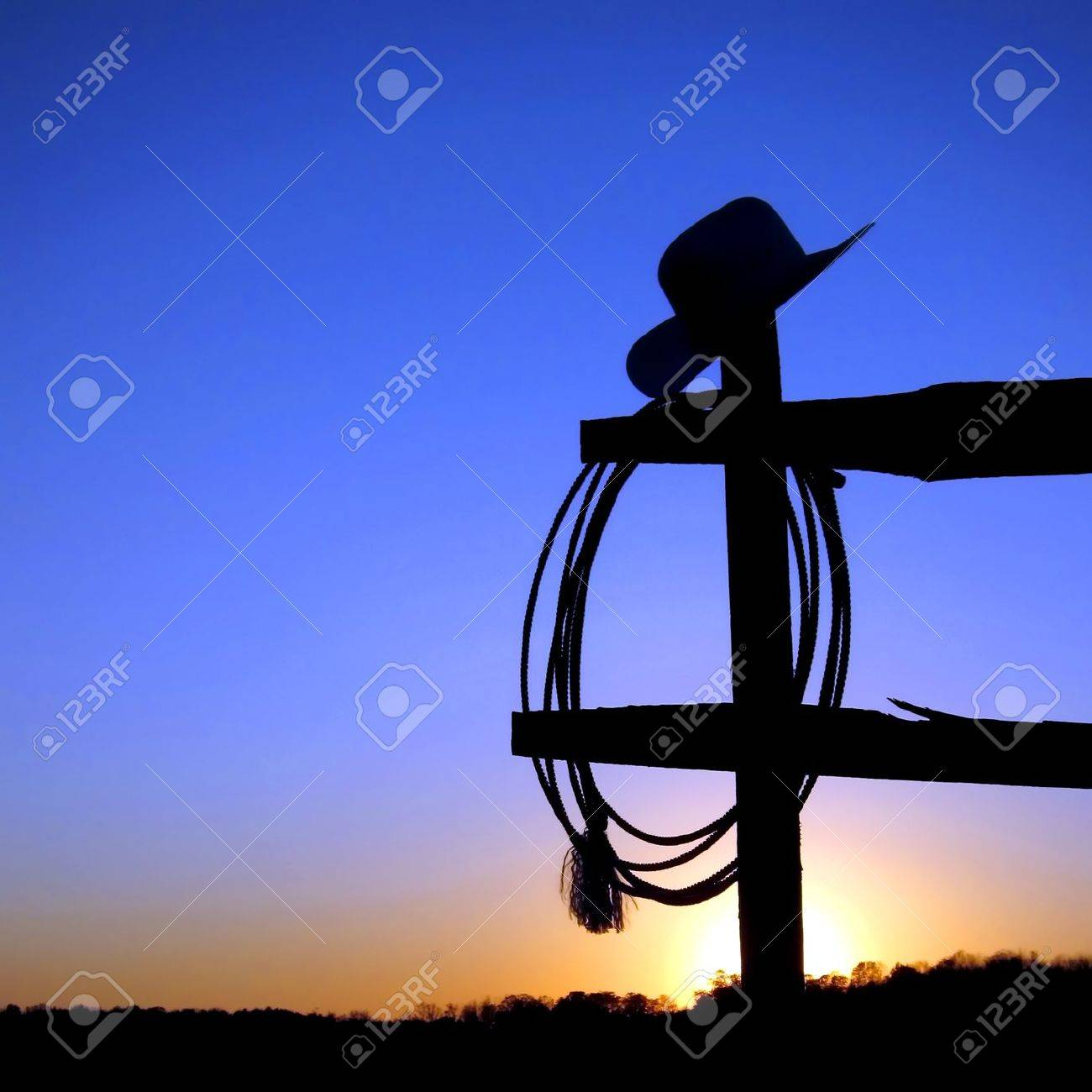 American West rodeo authentic cowboy hat and lariat lasso hanging on a ranch fence post in backlit silhouette over blue sky at sunset Stock Photo - 11241337
