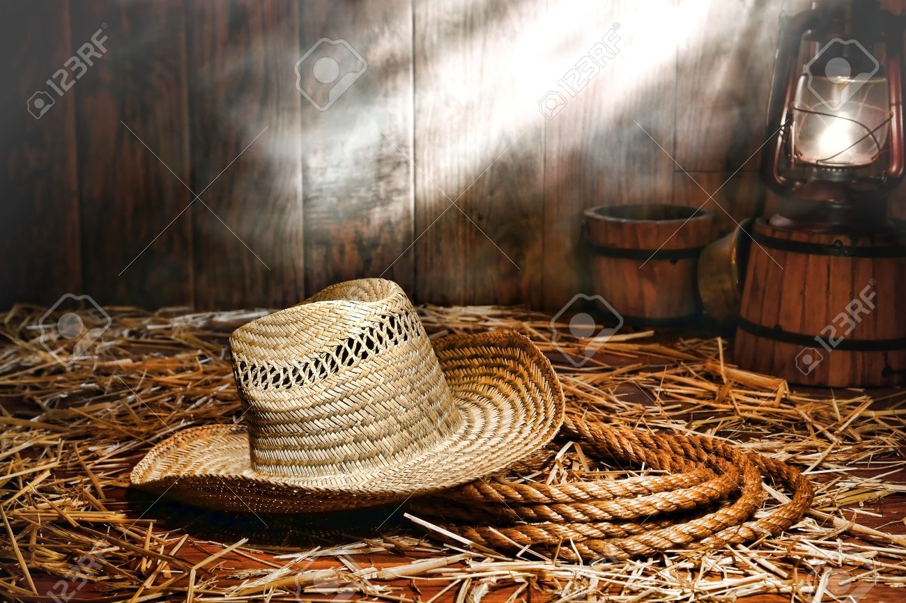 Old farmer straw hat over a sisal ranching rope on wood floor covered with loose hay lit by an antique kerosene lantern style oil lamp in an antique ranch barn with dust and smoke in diffused light Stock Photo - 11648220