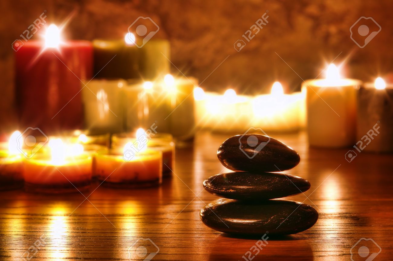 Symbolic Zen black polished smooth stones cairn stack and candles soft glowing in a spiritual religious temple for a meditation and reflection journey Stock Photo - 12186998