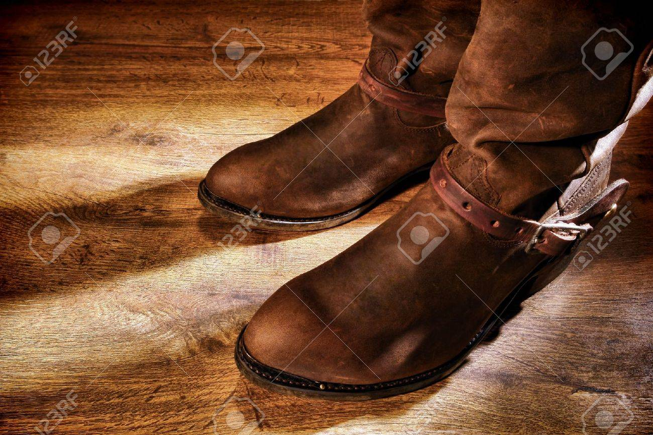 American West rodeo cowboy traditional working ranching boots with old leather Western riding spur straps on distressed grunge wood floor Stock Photo - 12543295