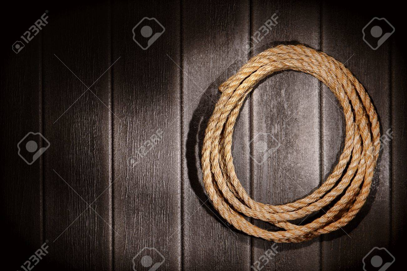 American West rodeo natural hemp fiber rancher rope for ranching and steer roping on grunge vintage barn wood wall background Stock Photo - 12837886