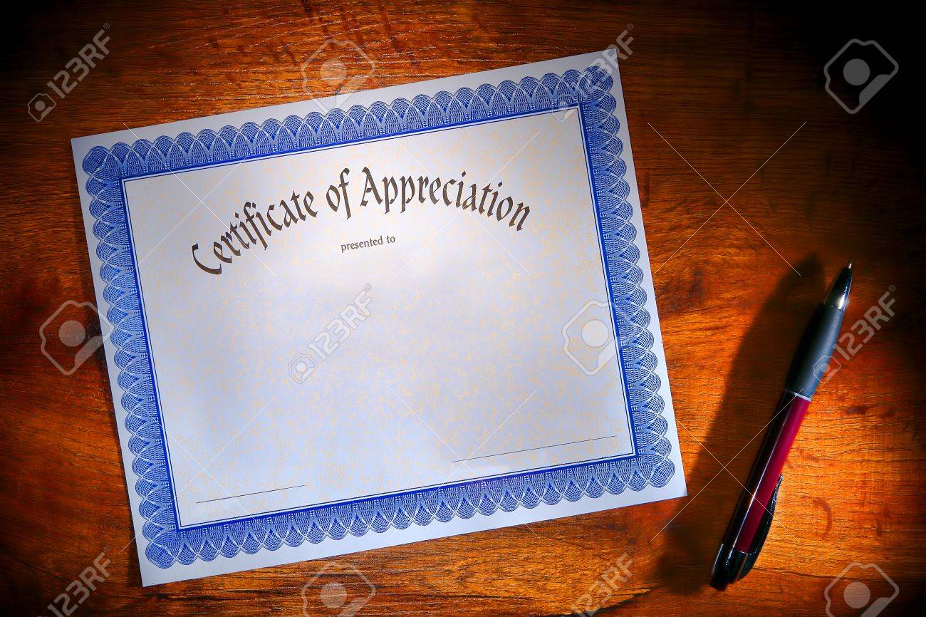 Certificate of appreciation reward blank paper document ready to fill out with text and ballpoint ink pen for signature on a wood desk Stock Photo - 12837885