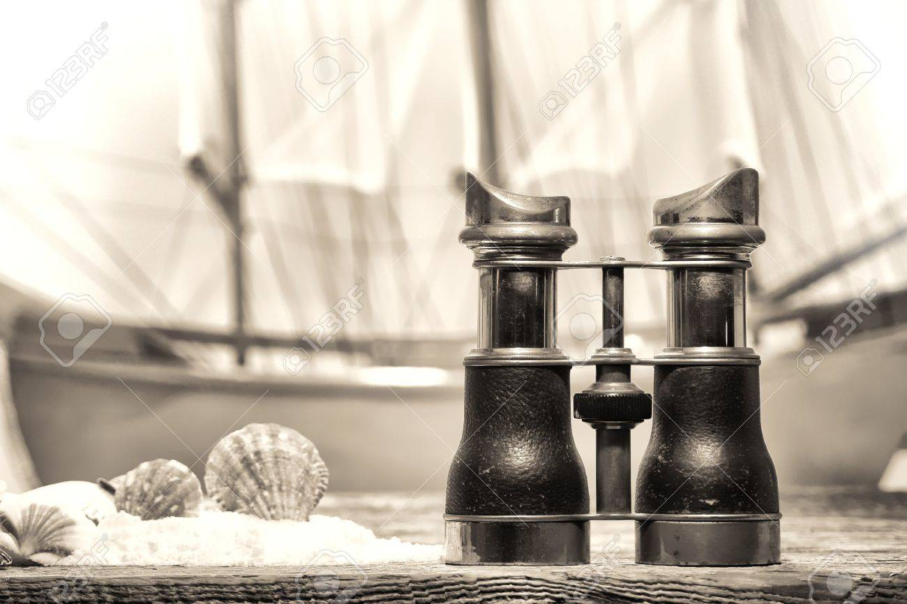Antique Binocular On An Old Seashore Resort Wood Pier Deck With Seashells Sand And A
