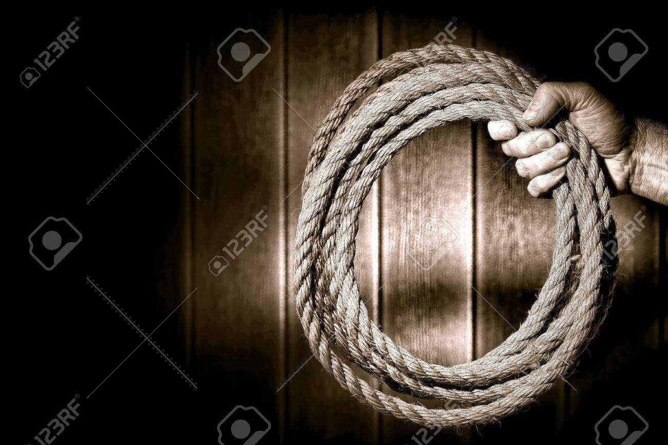 Rugged rancher cowboy hand firmly holding a ranching rope in a loop in an old rustic barn with dramatic light in nostalgic sepia Stock Photo - 13080799