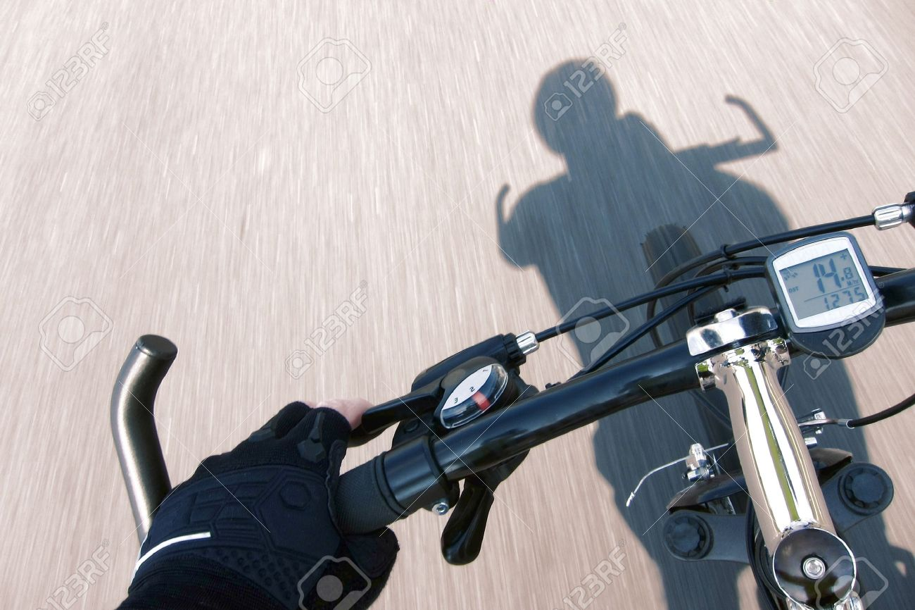Cyclist hand with racing glove holding handlebar and pulling brake lever rider point of view on a speeding mountain bicycle over a fast road with speed motion blur effect and cyclist shadow Stock Photo - 13264980