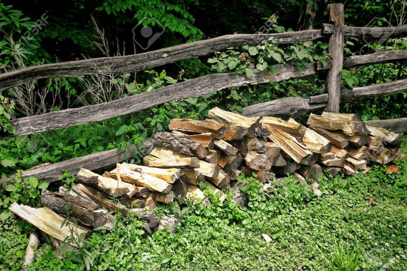 Pile of split fire wood logs against an old rail and post fence pile of split fire wood logs against an old rail and post fence in the woods baanklon Gallery