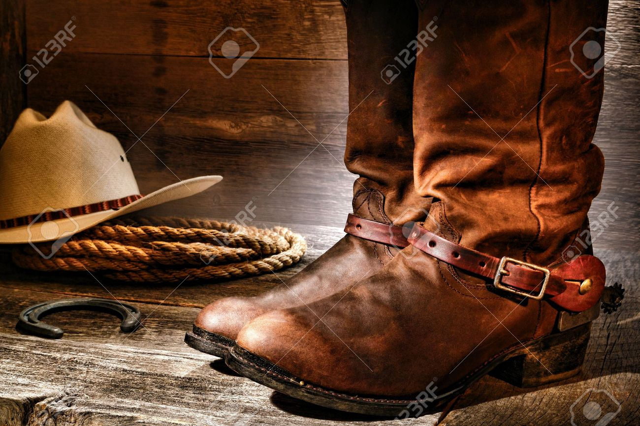 American West rodeo cowboy pair of traditional leather roper style western riding boots with authentic ranching spurs with hat and rope on an antique wood floor in an old ranch aged wooden barn Stock Photo - 15544316