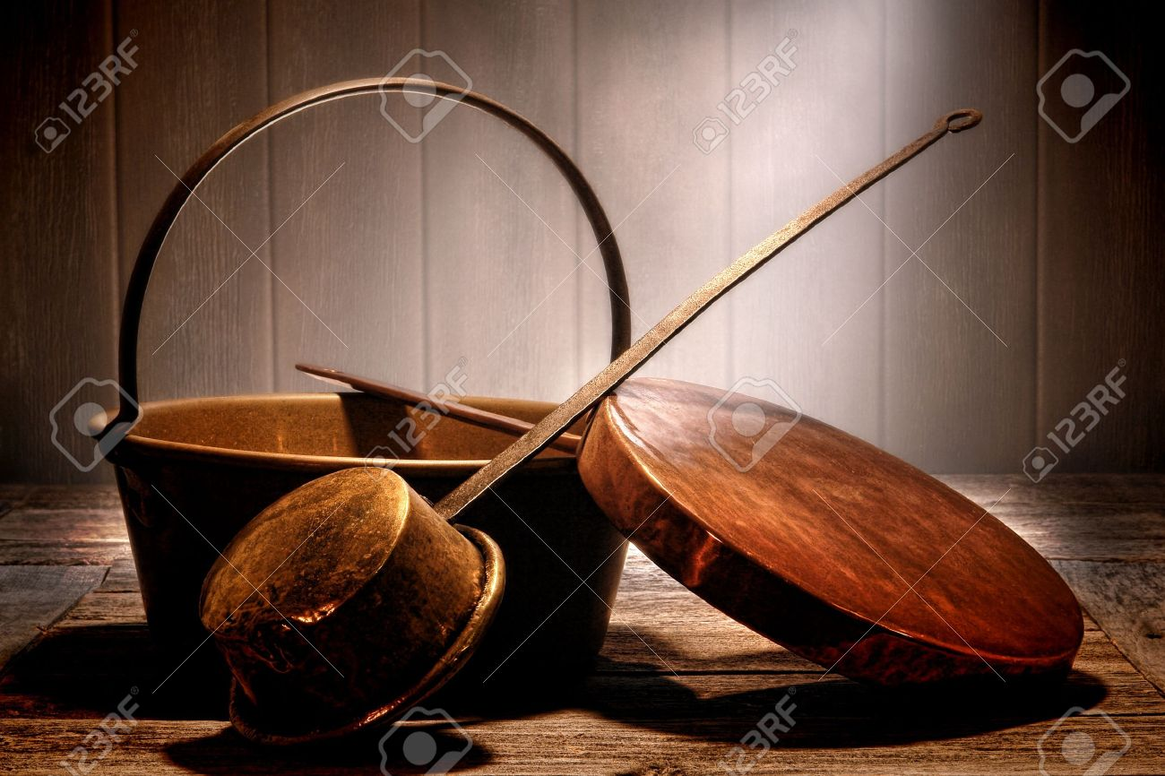 Old copper and brass metal pots and pans cooking utensil with forged steel handles on a weathered prep wood table in an aged antique kitchen in a historic home Stock Photo - 17564393