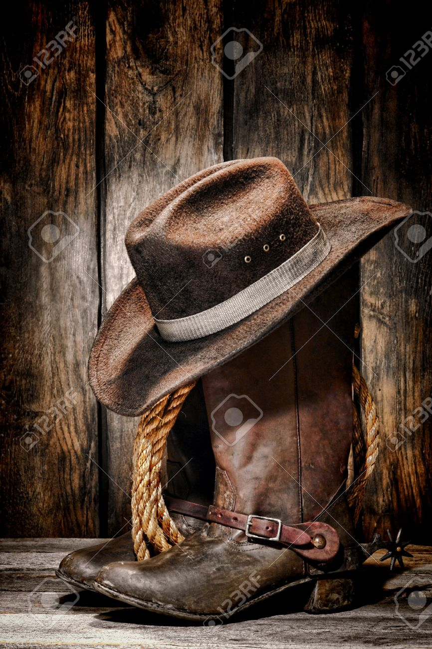 rodeo cowboy dirty and used black felt hat atop worn and old leather  working rancher boots 115e5620f1a