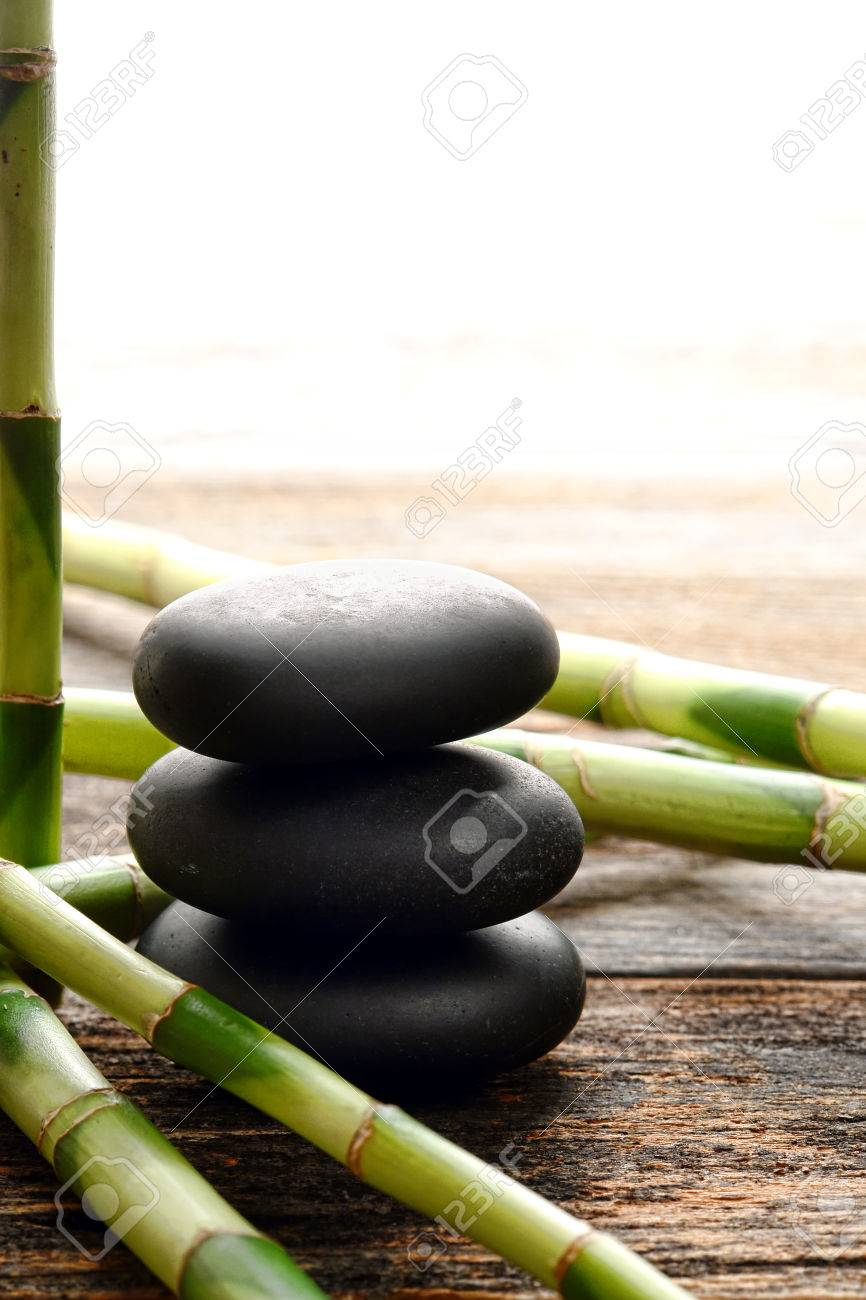 black smooth polished massage stones stack in a zen style