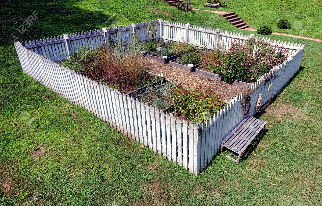 Antique Colonial Garden With Old Fashioned White Picket Fence
