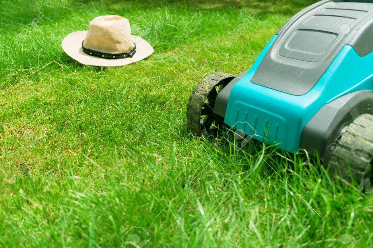Lawn mower mowing green grass and a sunhat. Summer work in the garden. - 128797587