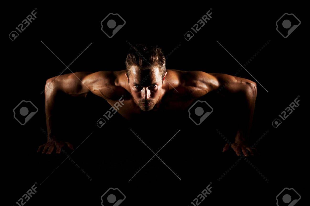 Man with focused eyes doing pushups on black background Stock Photo - 16821254