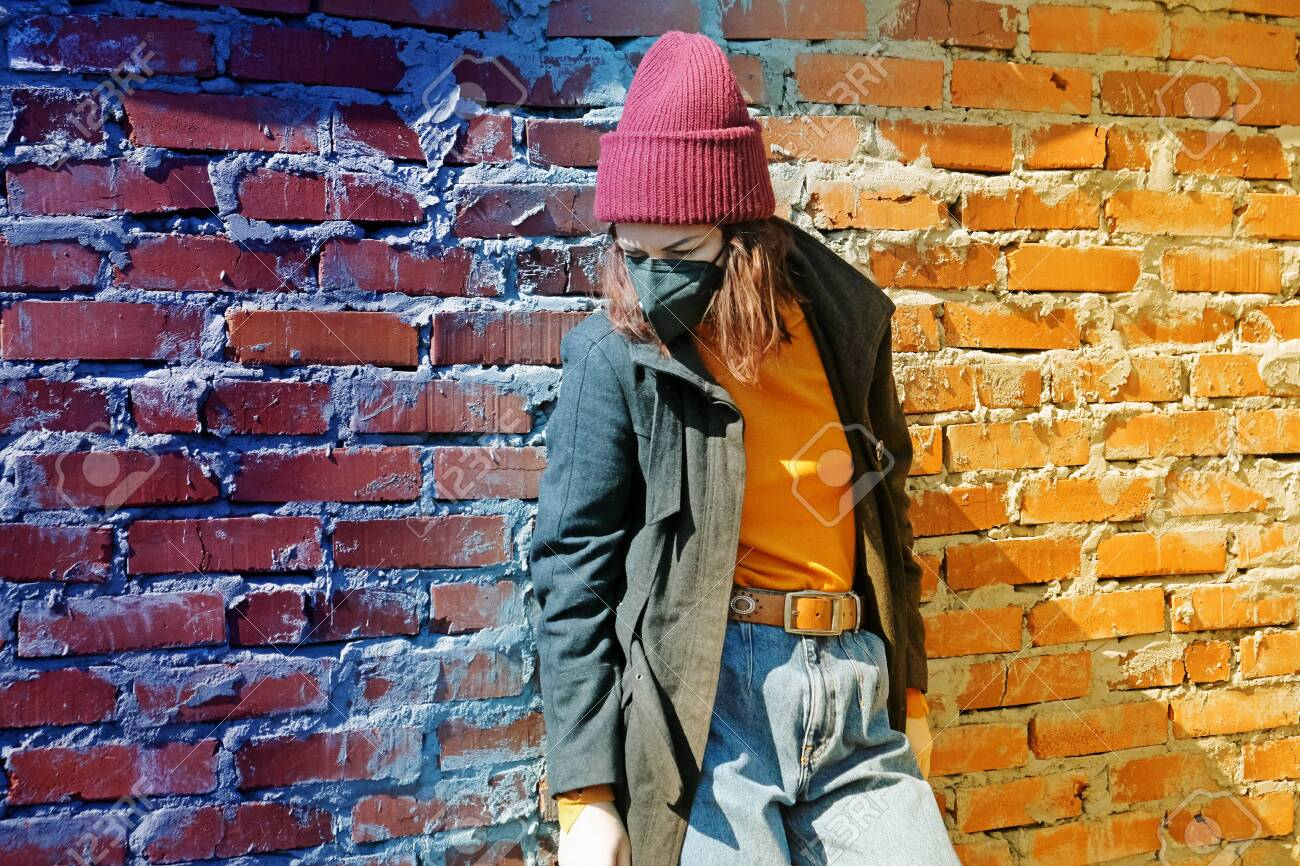 A sad girl in outerwear and a hat stands behind a brick wall in a black mask from the coronavirus - 148320574