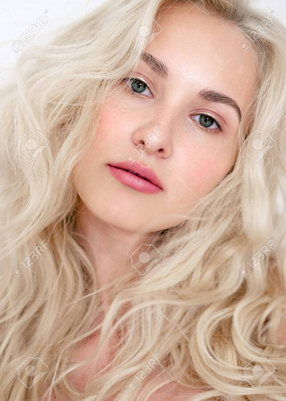 Portrait of a beautiful blonde model with lokans with natural makeup. Fashionable shiny marker on the skin, lip gloss, makeu - 141445276