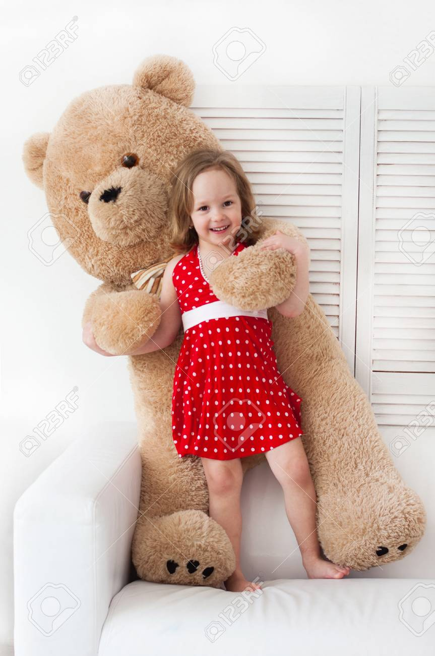 67e8e7ad5547 Happy little girl in red dress hugging a giant plush teddy bear. Friendship  and love