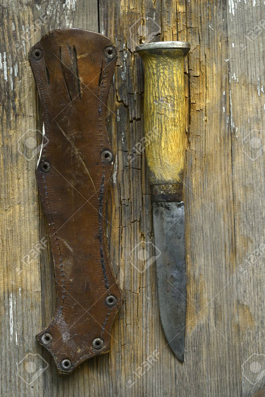 traditional Finnish knife puukko and sheath on a wooden background